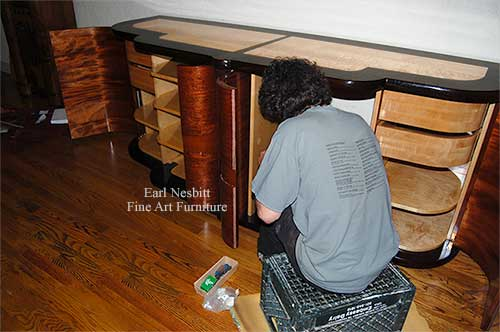 Earl installing retractable doors on custom made art deco cabinet
